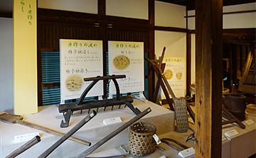 ↑展示品 開拓者のくらし 米作り 米作りの流れ 木製スコップ 馬鍬 苗かご 鎌。