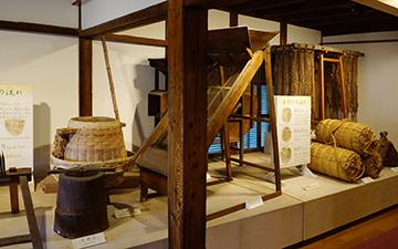 ↑展示品 開拓者のくらし 米作り 米作りの流れ 木摺臼 土摺臼。