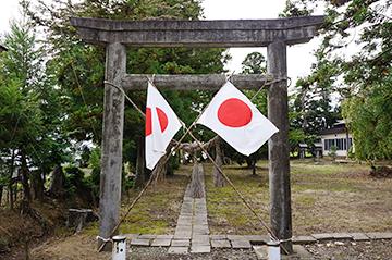 ↑国旗が掲揚されている三柱神社鳥居。